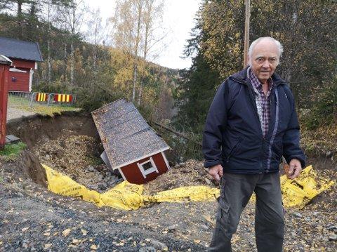 FRUSTRERT: Frank Engevold ble rammet av flommen i august, men venter fortsatt på at forsikringsselskapet skal igangsette opprydding på tomta i Spikdalsvegen. Uthuset i bakgrunnen er fullt av antikviteter, men det trekker i langdrag å få tømt det.