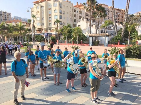AVMARSJ: Kvikne skolemusikk klare til avmarsj under korpsparaden med 15 spillende ungdommer og seks voksne blåsere. Dirigent Lage Robak dirigerer med norsk flagg.