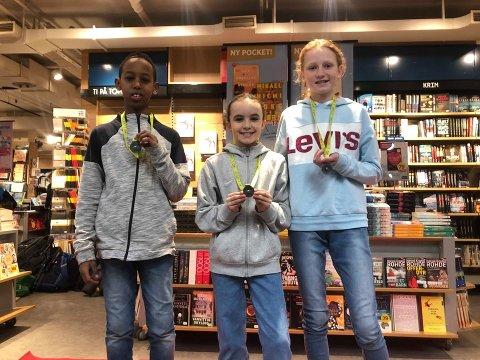 VINNERE: Ahmed Mohammed, Sara Sanderlien og Benedicte Lømo viser fornøyd frem medaljene sine, som er et bevis på at de er Hedmarks beste lesere.