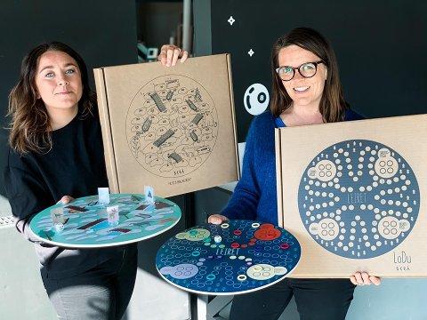 PÅSKEUNDERHOLDNING: Linnn Wold og Anita Ulvebne viser fornøyd frem de nye brettspillene sine, som de håper kan underholde folk i påsken.