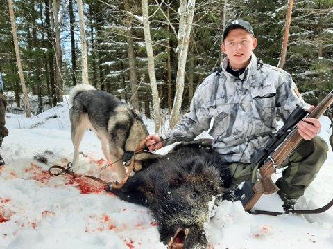 UNG JEGER: 18 år gamle Herman Lau fra jaktlaget til Halvor Sveen med villsvinet som ble felt på Sjølisand lørdag.