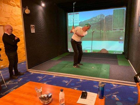 INNENDØRS: Vegard Strand trener i golfsimulatoren. Makker Terje Johansen følger med.
