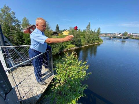 MINNES: Statsforvalter Knut Storberget var med på minnearrangementet i Elverum 22. juli. Her kaster han en rød rose i Glomma for å hedre de 77 som ble drept for 10 år siden.