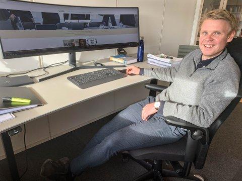 FET SKJERM: Stian Storsveen viser fram den store, buede skjermen på kontoret