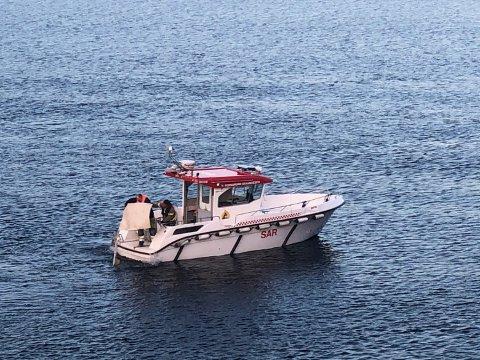 Her plukker mannskapene ombord i brannbåten opp vrakrestene fra Frierfjorden.