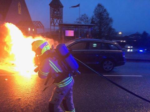 Det var full fyr i motorrommet på bilen da brannvesenet kom  fram.