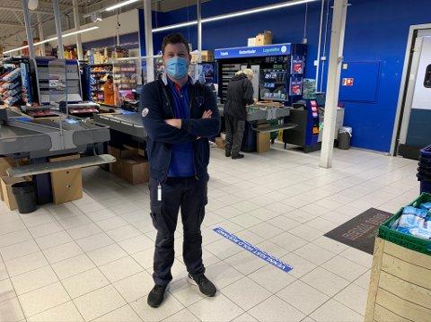 Thomas Klamerholm, kjøpmann på Rema 1000 Vallermyrene lovet at han smilte da PDs fotograf trykket på utløseren. Han legger ikke skjul på at det er ekstra tungt å jobbe med munnbind, men sier at de holder ut så lenge de må.