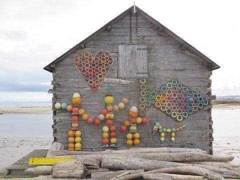 I Skallelv har noen plukket søppel i fjæra og laget et fint kunstverk på en naustvegg.
