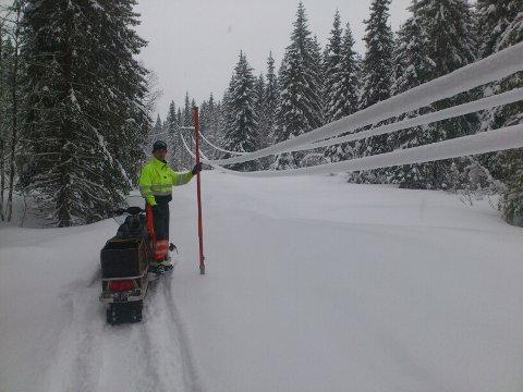 Livsfare: Her er strømmen koblet ifra mens montør Arne Haugen banker av snøen (arkivfoto)