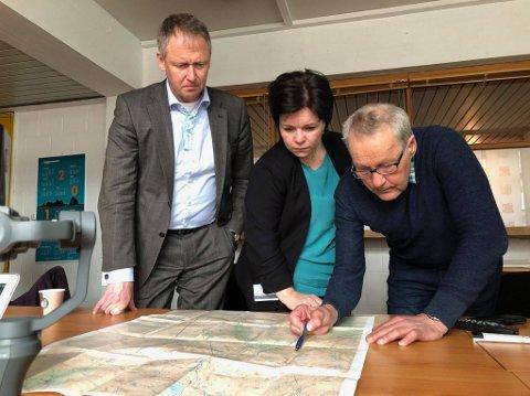 Rådmann Robert Pettersen (t.v.), kommunikasjonssjef Connie Slettan Olsen og Ståle Lysfjord studerer kart over området der raset har gått.