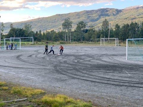 Mange barn og voksne er til stede ved fotballbanen torsdag ettermiddag.