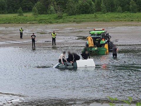 Her står pickup'en med ungdommene fast i elva. En traktor står klar til å forsøke å dra de på land.