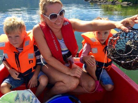Martin (6), Annette og Emmeline (6) er fornøyd med fangsten. - Vi fikk mange store. De små kastet vi uti igjen. Det er viktig, sier Annette.