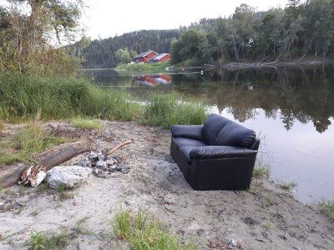 LUKSURIØS BÅLPLASS: En turgåer i Hønefoss undres over plasseringen av denne sofaen rett ved elva.
