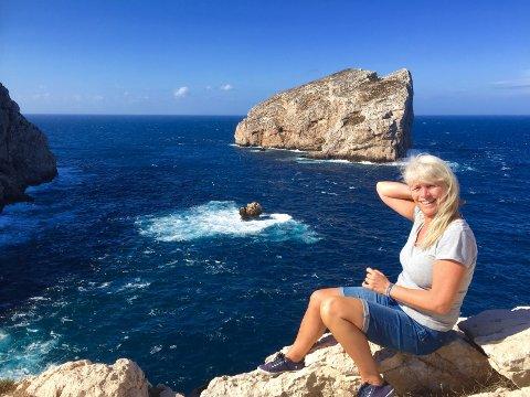 REISEGLAD: Gunn Kari liker å oppleve nye steder, her er hun foran en formidabel utsikt på øya Sardinia. Smilet sier alt!