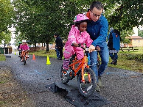 """Mestring: Barna i Eikli barnehage opplever glede og mestring med """"sykkelskolen"""". Her ser vi Marius Blytt hjelper Siham over sykkelrampen. Synne og Tjara gjør seg klar til å følge etter."""