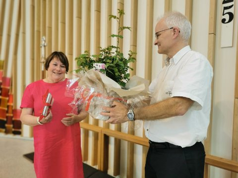 Sogneprest Tor Magnus Amble med gode ord og blomst til pensjonisten
