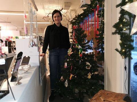 MER PYNT: Anita Hansen hos Minas kreative hjørne viser frem den fine pynten barn har laget og hengt opp på treet i vinduet i butikken. Det er plass til mer.