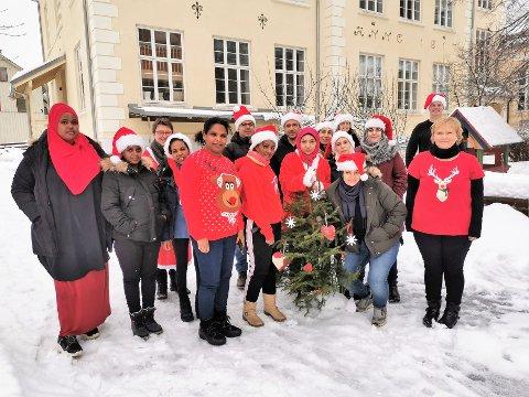 JULESTEMNING: Det har vært julestemning på voksenopplæringen mens deltakerne har skrevet om jula i hjemlandet. Lærer Turid Ree Bjørnerud nr. tre fra venstre, lærer Siri Andersen helt til høyre foran Jørn Langeland, og lærer Anne Marit Lindgaard nr. tre fra høyre bakerst.