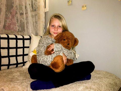 Amalie Lindmark Engebretsen har fortsatt et kjært forhold til bamsen hun holdt på å miste på vei til vinterferie i fjor. Foto: Privat