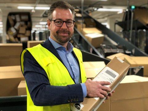 Pressesjef John Eckhoff med en av cirka fire millioner pakker som går gjennom Posten og Brings Logistikksenter Oslo før jul.