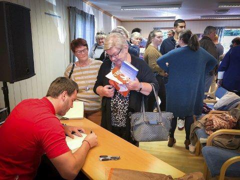 SIGNERING: De fleste som dukket opp på boklanseringen reiste hjem med en signert bok, og Martin Skolbekken tok seg god tid med lokalbefolkningen. Foto: Veronika Sletta