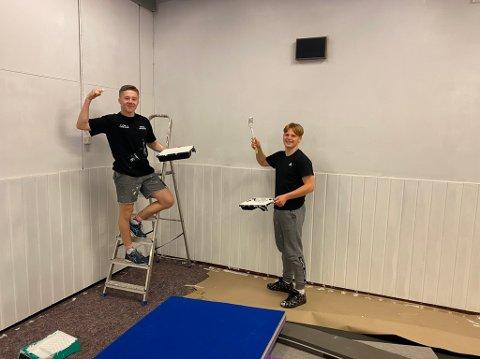 MED PENSEL OG MALING: Kasper Øverby (til venstre) og Mikkel Nybakk maler veggen i det lille aktivitetsrommet til Skedsmo bryteklubb i Tærud fjellhall. Nå er idrettsanlegget stengt – og åpnes trolig aldri for aktivitet igjen.
