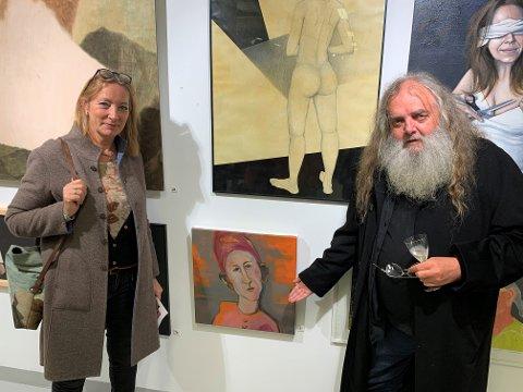 """UTFLYTTEDE NESBUER: Heidi Asdahl og Rolf Flatmo bor i Oslo, men kommer fra Årnes og Fenstad. Her står de ved Heidis maleri """"Hva var det jeg sa?"""". Rolf deltar med fotokunst fra Vestlandet."""