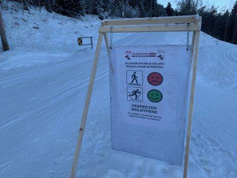 Ved lysløypa i Tæruddalen står det skilt som oppfordrer gående til å ikke oppholde seg i skisporene.