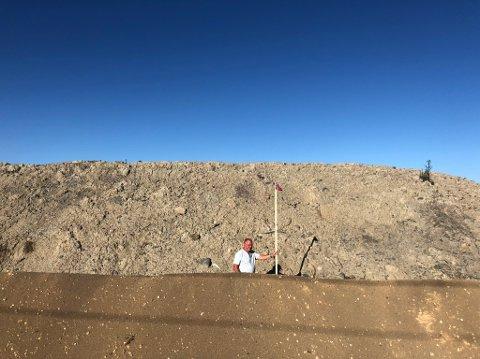 Støyvoll av dimensjoner: – Den har blitt altfor høy, sier Arnfinn Berntsen. Lista han har i hånda viser makshøyden vollen skal ha. Den består av tilkjørt overskuddsmasse fra byggeprosjekt i Lørenskog. Massen foran er sandjord fra området som skal dekke vollen.