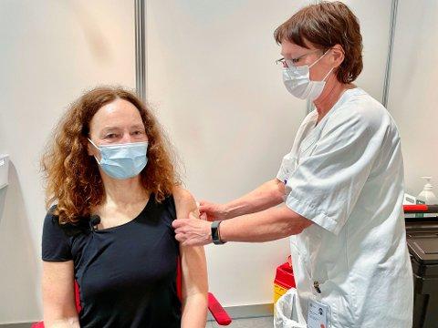 Sykepleier Ellen Lødemel setter plaster på stikket, etter at direktør i Folkehelseinstituttet, Camilla Stoltenberg, ble vaksinert mot covid-19 torsdag. Stoltenberg oppfordrer alle til å gripe sjansen når de i sommer får tilbud om koronavaksine.