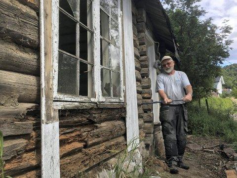 NYTT VIRKE: Byggmester Jon Grette avdekker de råtne tømmerstokkene som må byttes ved å jekke opp hytta i sommer. Nå har historielaget fått 55 000 kroner til videre arbeid.