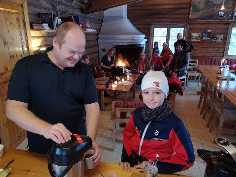Harald Sævold serverer gløgg til Theodor (11). Gløgg og vafler gjorde rask slutt på skuffelsen over at grøtkjelen var tom.