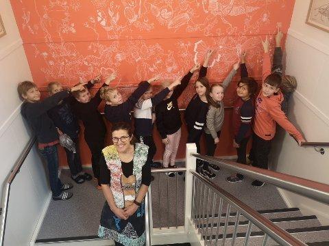 VEGG: Pippi Ferner foran eleven som studerer veggen med tegninger som Pippip har laget til skolen.