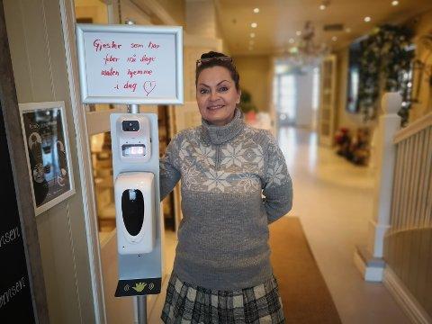 EGEN VRI: Holmsbu badehotell har feberautomat i inngangsen. Over automaten står en plakat som Elizabeth Nordhagen Bøifot har skrevet om at gjester med feber må lage maten hjemme mens de er syke. – Det er jo litt hyggeligere enn bare en upersonlig plakat om å holde seg hjemme, smiler hun.