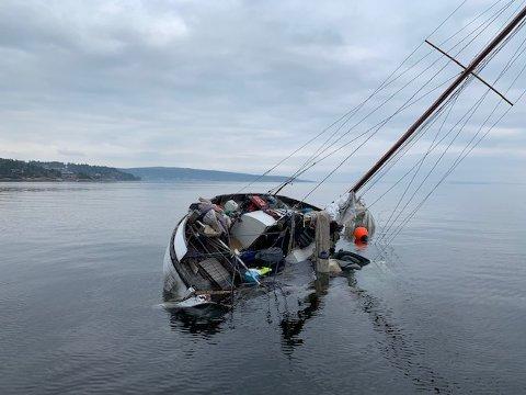 GÅR NED: Grunn til å bli bekymret over seilbåten som nå ligger delvis under vann.