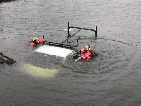 UNDERSØKER BILEN: Det er dykkere på stedet og undersøker bilen innvendig.