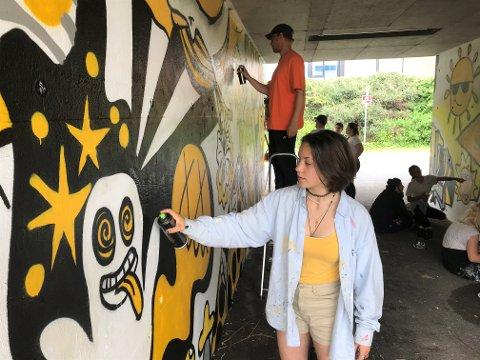 FARGERIK KUNST: Kine Kirkegaard (bildet) og en gjeng unge har jobbet sammen i tre uker i et tett samarbeid med profesjonelle graffitiartister. Det har resultert i fargerike underganger ved Lofterød, Hasle, Framnes, Gjekstad, Varden og Mosserød.