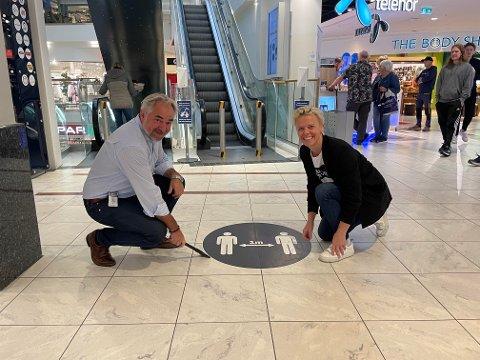 SKAL BORT: Merket som ber om at kundene holder minst én meters avstand kan skrapes bort fra gulvet i Hvaltorvet. Det er senterleder Geir Ellefsen og markedskoordinator Inger-Anne Hem-Andersen glade for.