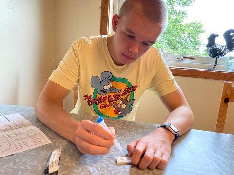 TESTER HJEMME: På kjøkkenbordet hjemme i Fredrikstad tester videregående elev Max Bølum seg før han går på skolen. – Jeg står opp, tar testen og venter på resultatet mens jeg spiser frokost. Det tar omtrent 15 minutter før resultatet dukker opp, forklarer han. FOTO: Privat