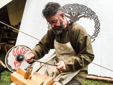 HÅNDVERK: Bjørnar Thengs fra Hafrsfjord vikinglag er blant dem som allerede er på plass i Landeparken. Her arbeider han fram en bue.