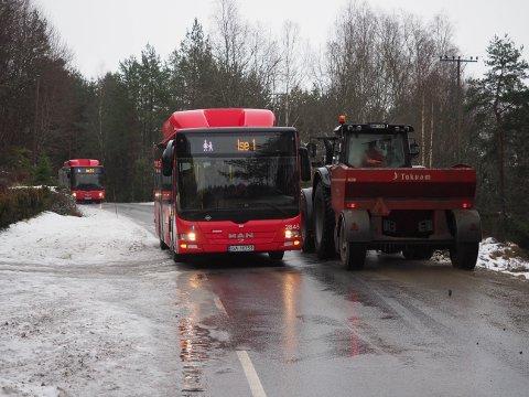 VENTET PÅ STRØBIL: Disse bussene sto mellom Ise og Varteig fram til det kom strøbil i formiddag. Her er en traktorfører ute og strør sand i veibanen i et forsøk på å gjøre forholdene bedre.