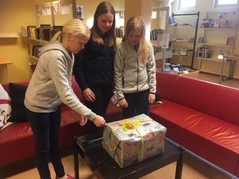 Bokgave: Elevene Ingrid Holmskau (fra venstre), Angelica Thon Johansen og Ida Synnøve Molander ved Grålum barnsekole, med bokgaven fra Sarpsborg bibliotek.