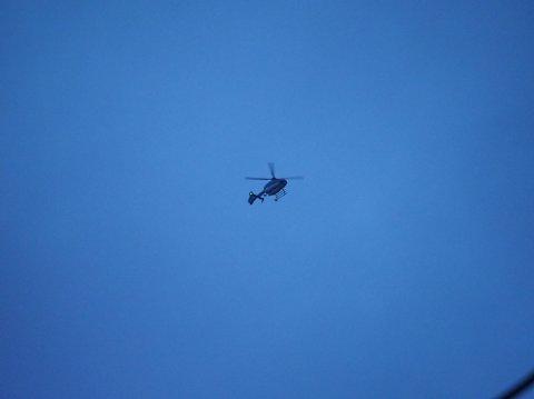 Politiets helikopter bistår i søket etter gjerningsmannen som skal ha løpt fra stedet.