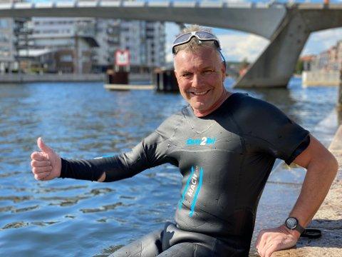 SLITEN, MEN BLID: Jan Tage Baller (53) gir fotografen tommel opp etter å ha svømt i tre timer og 56 minutter i Glomma.