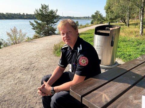 FLOTT OMRÅDE: Lars Erik Gutubakken (48) oppfordrer turfolket til å bruke kommunens fastmonterte griller nå som det er så varmt og tørt. Her sitter han på en av de mange benkene på Tjueklo med utsikt utover Glomma.