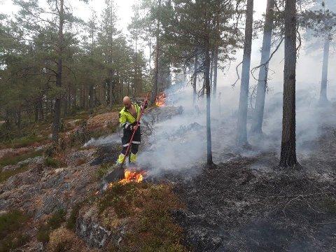 Kristian Billing fra Indre Østfold Brann og Redning i gang med slukking av skogbrannen.