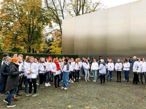 Her står Marker-elevene med hver sin rose ved minnesmerket for Berlin-muren.