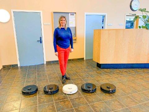 Avdelingsleder for hjemmetjenesten, Åshild Hamborg, viser fram støvsugerrobotene som er tatt i bruk av Marker kommune; én på bo- og servicesenteret, de fire andre i hjemmetjenesten.