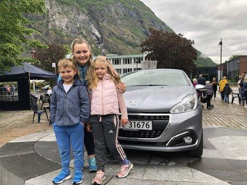 NY BIL: Tonje Mikkelsen saman med dottera Emilie og bonussonen Linus, begge seks år. Ho vart den stolte nye eigaren av ein Peugot 208 under avslutninga av Fjord til fjell søndag ettermiddag. (Foto: Anne Kauppi/ÅTIL)